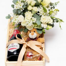 This Champagne, Flower and Teddy Hamper consists of a floral tin aarrangement, bottle of Jc Le Roux sparkling wine and a soft teddy. Delivery local area.